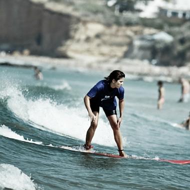 Waterman School Alumna aprendiendo surf en la escuela de surf de conil